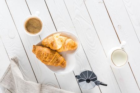 Medialunas con café y leche en la mesa de madera Foto de archivo - 80730097