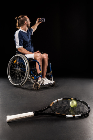 paraplegico: tennis racquet with ball and disabled sportsman taking selfie behind Foto de archivo