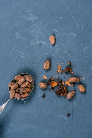 top view of cocoa beans in metal spoon on dark tabletop