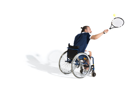 Disabled young sportsman in wheelchair playing tennis Stockfoto