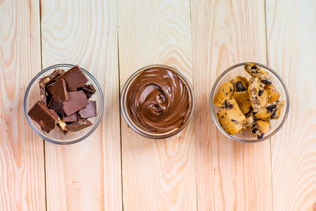 biscuits: top view of cocoa spread with cookies and pieces of chocolate on wooden background