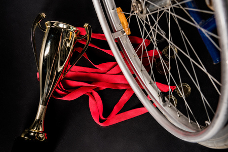 paraplegico: wheelchair standing on gold medals with red ribbons and champion goblet