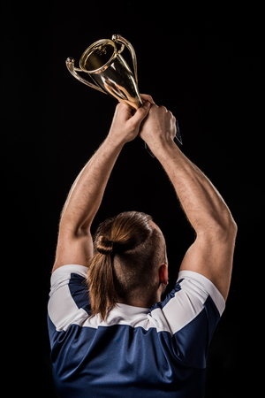 Back view of athletic young sportsman holding trophy isolated on black