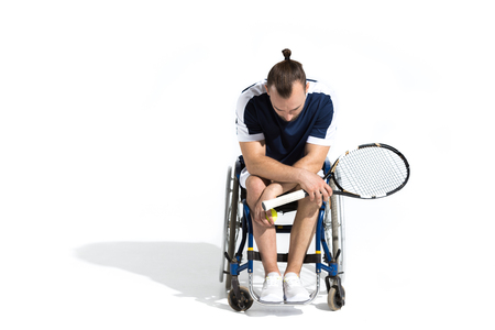 paraplegico: Disabled young man sitting in wheelchair and holding tennis racquet