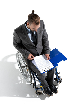 physically handicapped businessman in wheelchair looking at contract