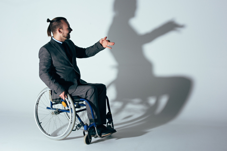 man in suit sitting in wheelchair making shadow of dog on white wall Stock Photo