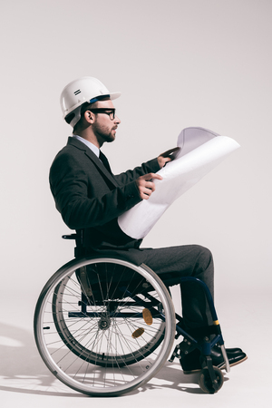 concentrated engineer in hard hat sitting in wheelchair and looking at blueprint Stock Photo
