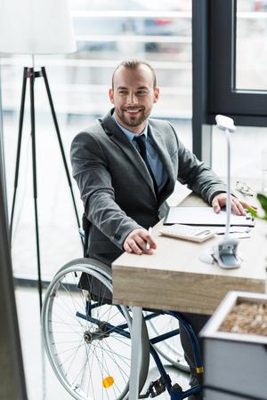オフィスで働いている車椅子にスーツで身体障害者の実業家 写真素材