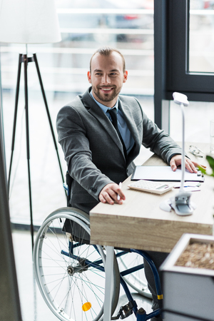 physically handicapped businessman in suit on wheelchair working at office