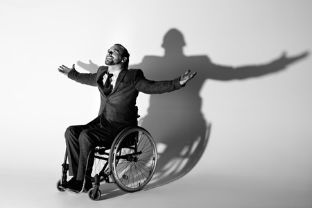 cheerful businessman in suit sitting in wheelchair gesturing with shadow on white wall
