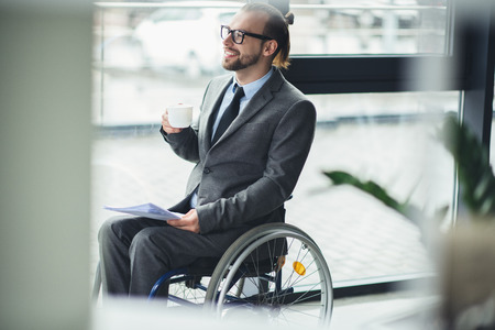 businessman sitting in wheelchair holding documents and cofee cup