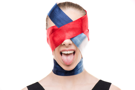 Woman with wrapped face with ribbons sticking tongue out