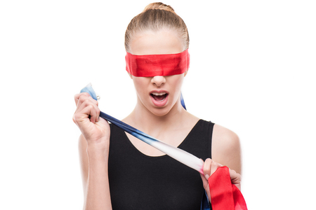 shocked gymnast in leotard with eyes covered with red ribbon
