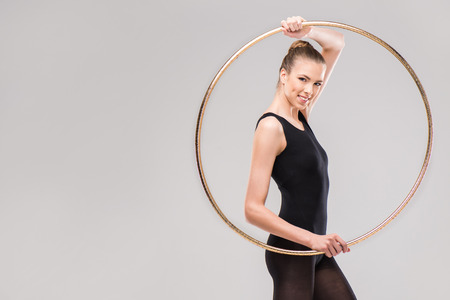 attractive smiling rhythmic gymnast in leotard posing with hoop Stock fotó