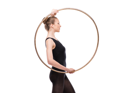attractive rhythmic gymnast in leotard smiling and posing with hoop