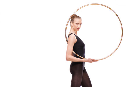 attractive rhythmic gymnast in bodysuit posing with hoop and looking at camera