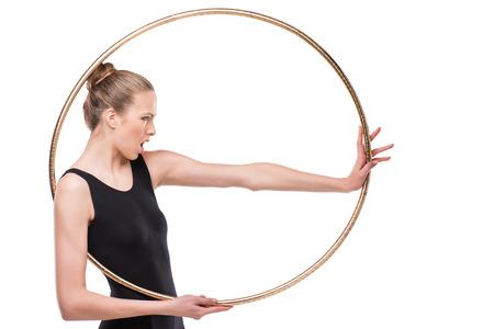 attractive emotional rhythmic gymnast in bodysuit posing with hoop Imagens