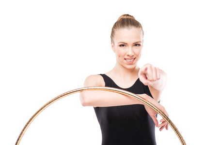 attractive rhythmic gymnast in leotard pointing with hoop