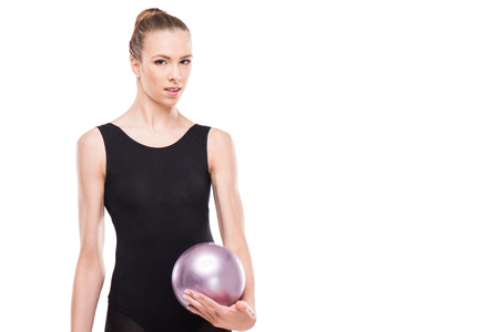 attractive rhythmic gymnast in leotard smiling and holding ball