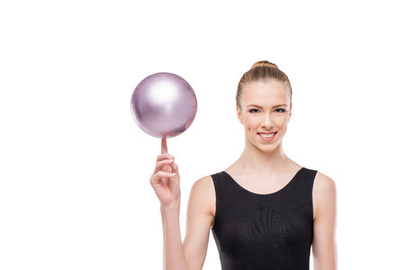 attractive rhythmic gymnast in leotard smiling and holding ball on finger