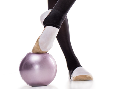 Close-up partial view of rhythmic gymnast exercising with ball