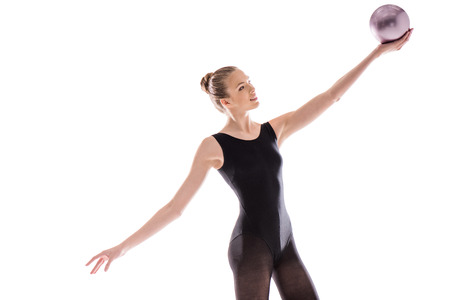 young sportswoman in leotard doing rhythmic gymnastics exercise with ball Stock fotó