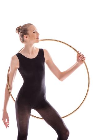 young sportswoman in bodysuit doing rhythmic gymnastics exercise with hoop Stock fotó