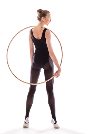 Back view of beautiful young sportswoman in bodysuit holding hoop