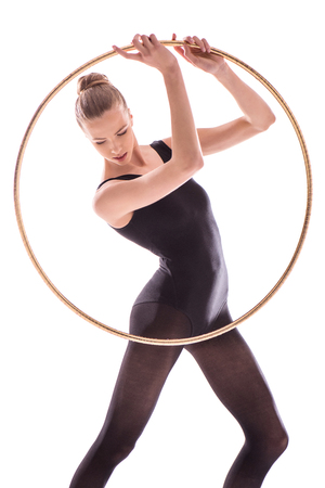 Attractive young sportswoman in leotard exercising with hoop