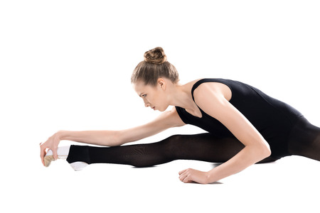Attractive young sportswoman training and stretching