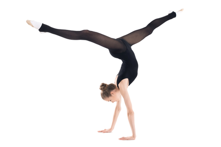 Athletic young woman in sportswear doing handstand