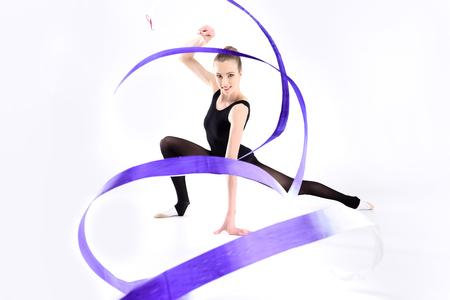 jonge sportvrouw uitoefening van ritmische gymnastiek met lint en glimlachen Stockfoto