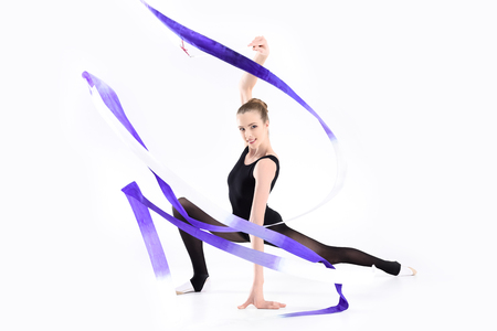 young sportswoman exercising rhythmic gymnastics with ribbon and smiling Stock fotó