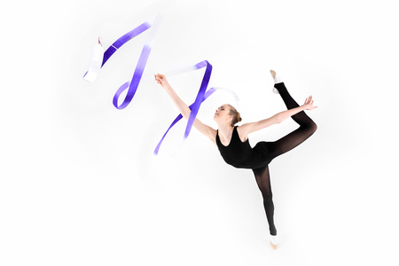 young woman doing gymnastics with ribbon isolated on white