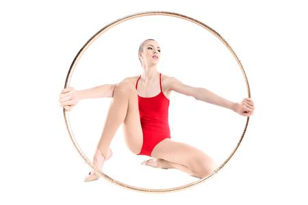 Sportive rhythmic gymnast holding hoop in hands