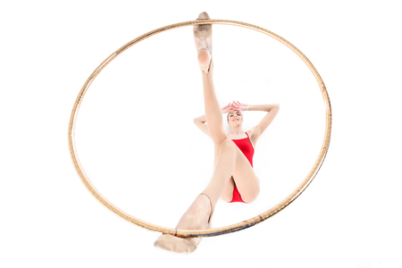 rhythmic gymnast holding hoop on legs