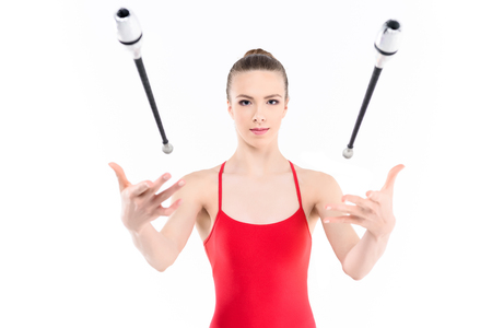portrait of rhythmic gymnast training with clubs
