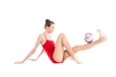 smiling rhythmic gymnast exercising with ball