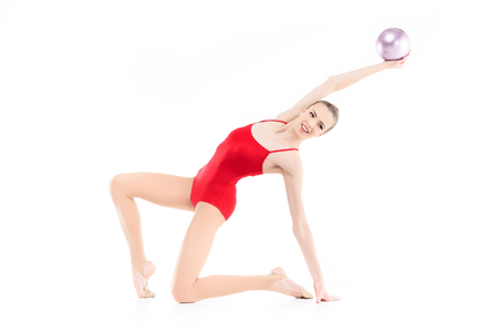 smiling rhythmic gymnast exercising with ball isolated on white