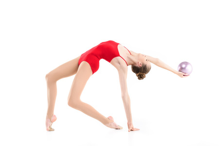 fit rhythmic gymnast exercising with ball