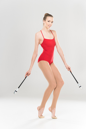 young smiling caucasian woman rhythmic gymnast exercising with clubs Stok Fotoğraf