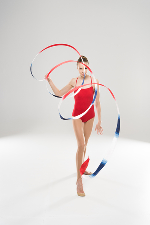 young caucasian woman rhythmic gymnast walking with colorful rope