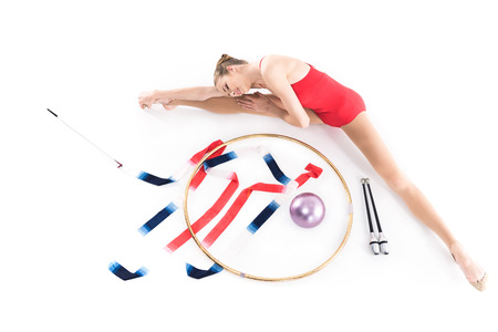 girl athlete stretching near rhythmic gymnastics apparatus