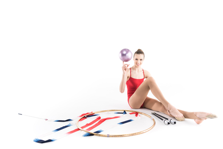 girl athlete sitting near rhythmic gymnastics apparatus and looking at camera Stock fotó