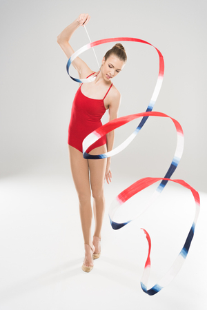 young woman rhythmic gymnast exercising with rope and looking down