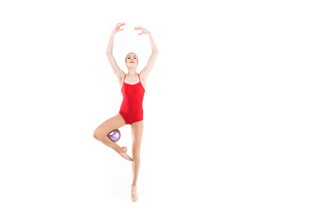young caucasian woman rhythmic gymnast exercising with ball