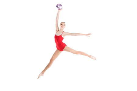 caucasian woman rhythmic gymnast jumping with ball