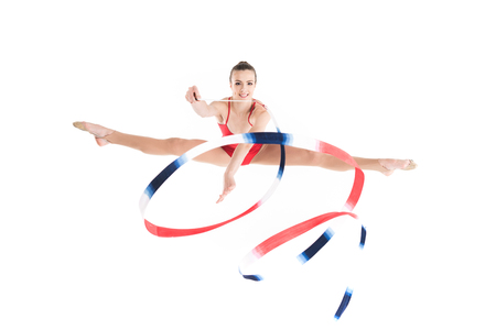 woman rhythmic gymnast jumping with colorful rope and looking at camera
