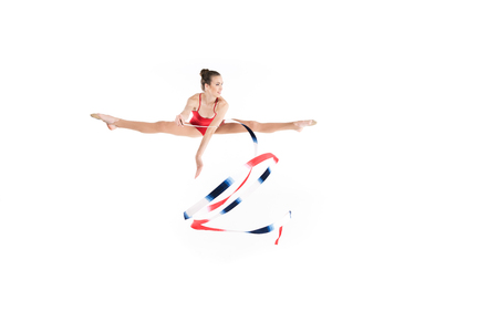caucasian woman rhythmic gymnast jumping with colorful rope