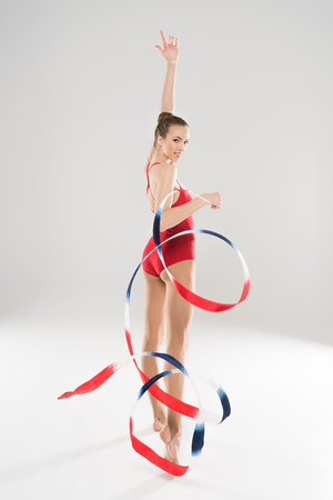 young woman rhythmic gymnast posing with colorful rope and looking at camera Stock fotó